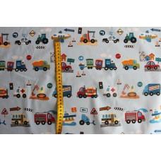 Lastbiler og biler i rækker på lys blå stof